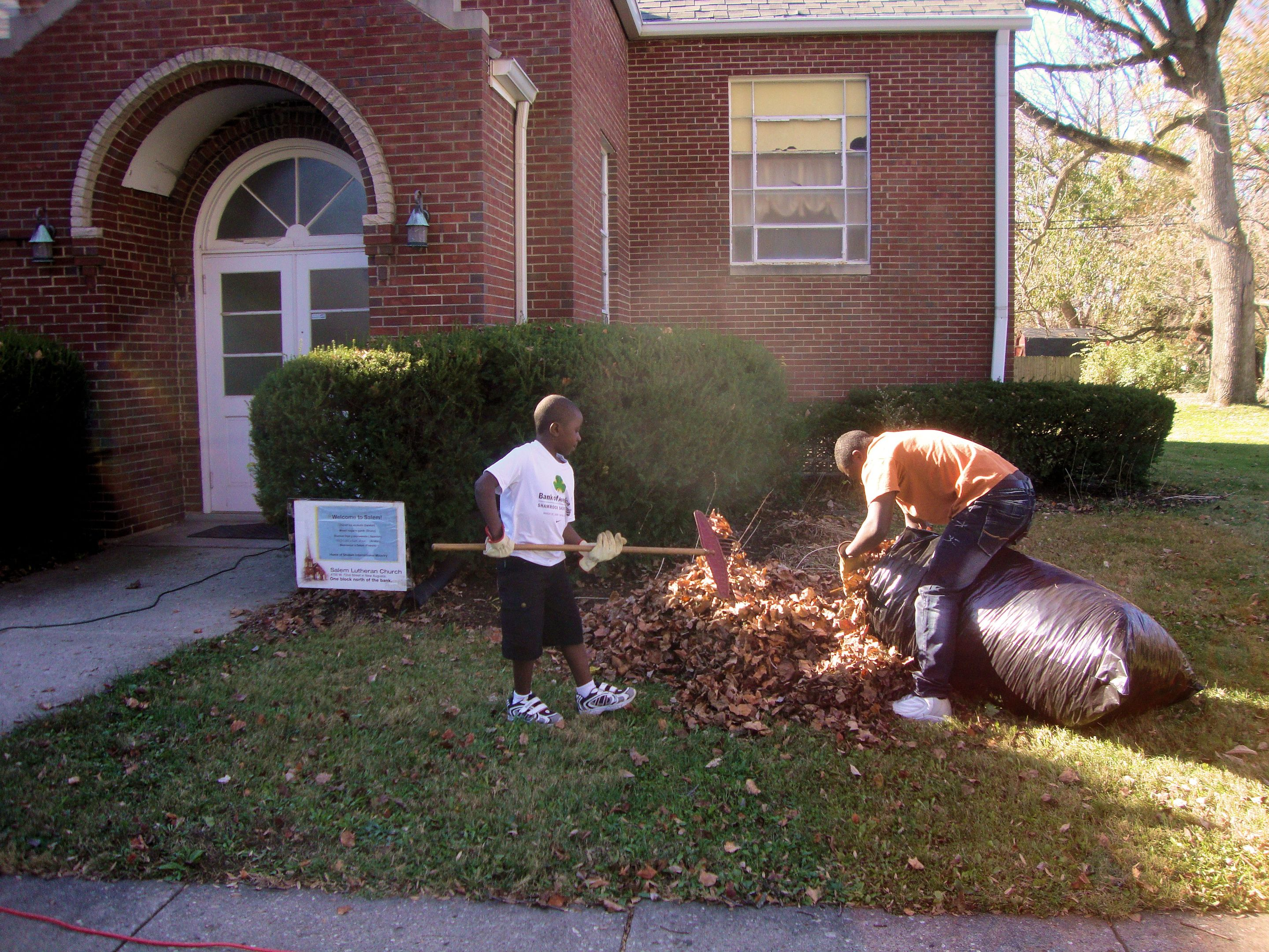 Adolphe and son Kalamo rake leaves during Salem fall work day.
